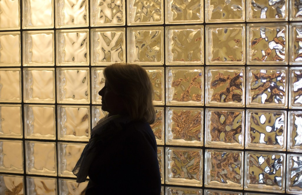 Behind Nancy Thompson of Cape Elizabeth is a glass wall honoring the memory of her son Timmy at the Center for Grieving Children in Portland.