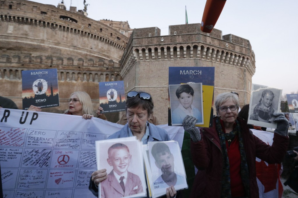 People hold up pictures of those who they say are victims of sexual abuse by priests as they gather during a twilight prayer vigil near Castle Sant' Angelo in Rome on Thursday.