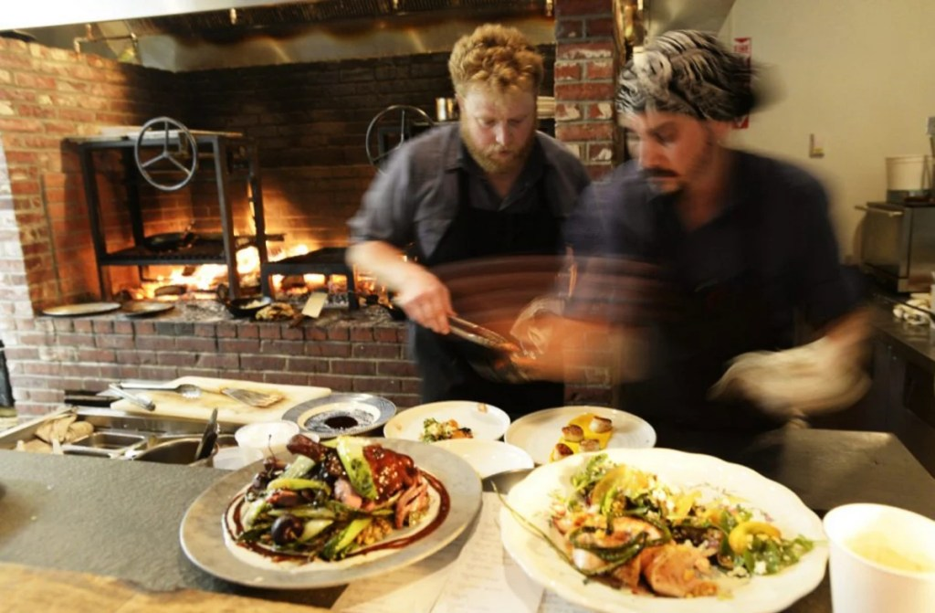 Cooks Matt Jauck, left, and Sean Kach prepare plates last July at Walkers Maine in Cape Neddick. The restaurant, awarded Four Diamonds this year, re-opens March 14 with a new spring menu.