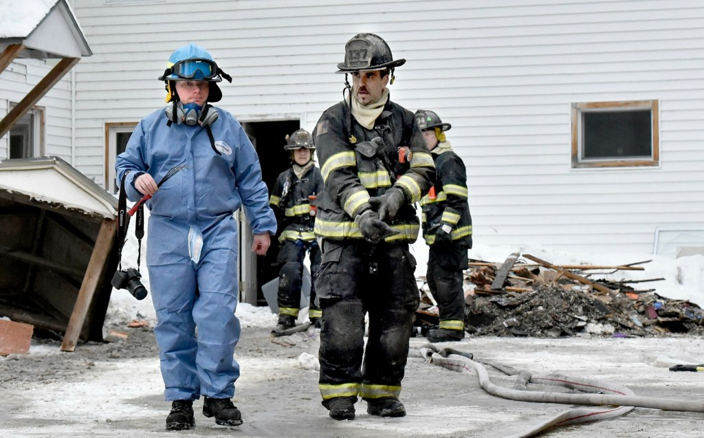 Jeremy Damren, left, of the state Fire Marshals Office, confers with a Skowhegan firefighter while investigating the cause of a fire at 386 Water Street in Skowhegan after fire broke out on Sunday, February 3, 2019.