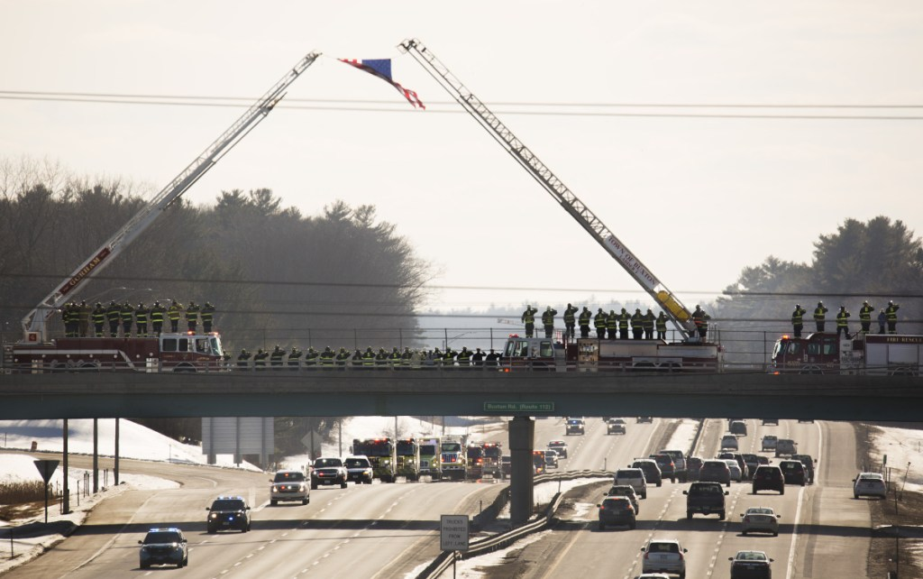 Firefighters line up Sunday afternoon on the Buxton Road bridge over the Maine Turnpike in Saco as a procession carrying the body of Berwick Fire Capt. Joel Barnes heads to the Old Orchard Beach Funeral Home, where a private family ceremony is expected to be held this week. Barnes died while battling an apartment building fire in Berwick on Friday.