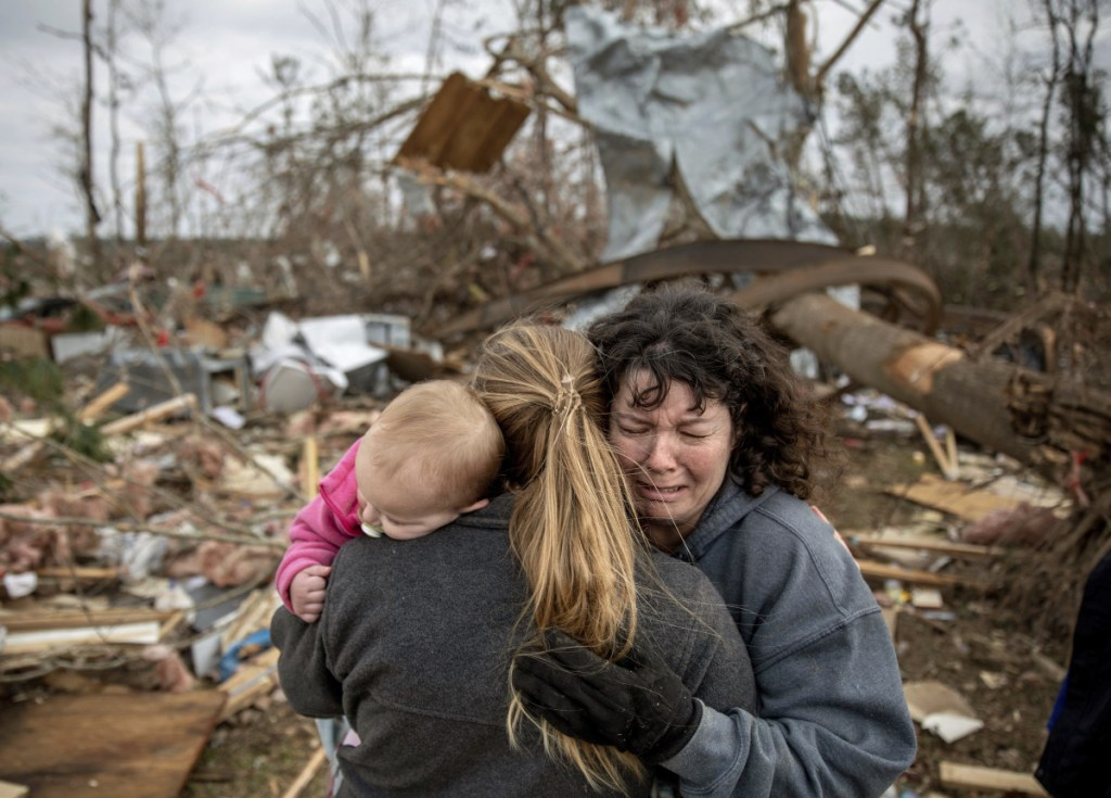 Carol Dean, right, cries while embraced by Megan Anderson and her 18-month-old daughter Madilyn at her destroyed home in Beauregard, Ala.