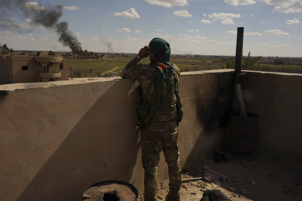 A U.S.-backed Syrian Democratic Forces fighter watches as smoke billows from an area still held by Islamic State militants in Baghouz, Syria, on Sunday.