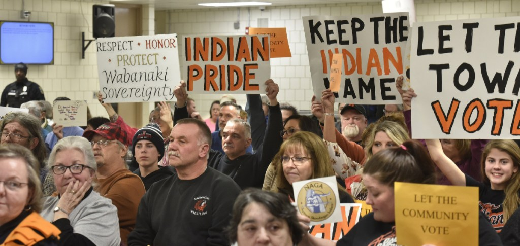 "People for and against using the ""Indians"" nickname and mascot in SAD 54 schools show signs to school board members during the meeting Thursday night in Skowhegan."