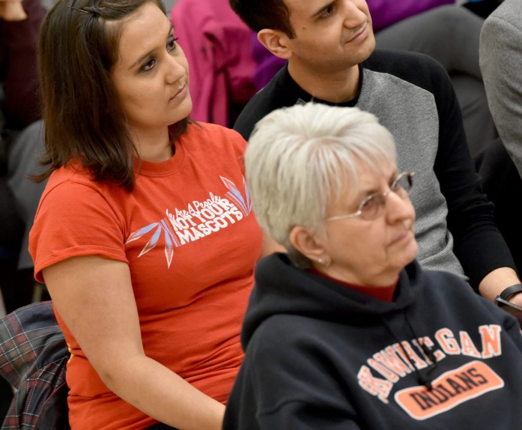 """Malian Dana of Indian Island, back left, sits with a shirt that reads """"We Are A People Not Your Mascot"""" during a school board meeting at Skowhegan Middle School in 2016."""