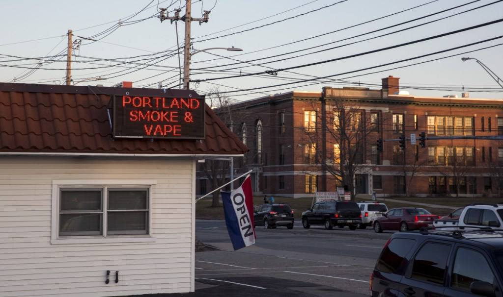 Portland Smoke & Vape shop at 585 Broadway, in the foreground, sits across the street from Daniel F. Mahoney Middle School, in the background, in South Portland.