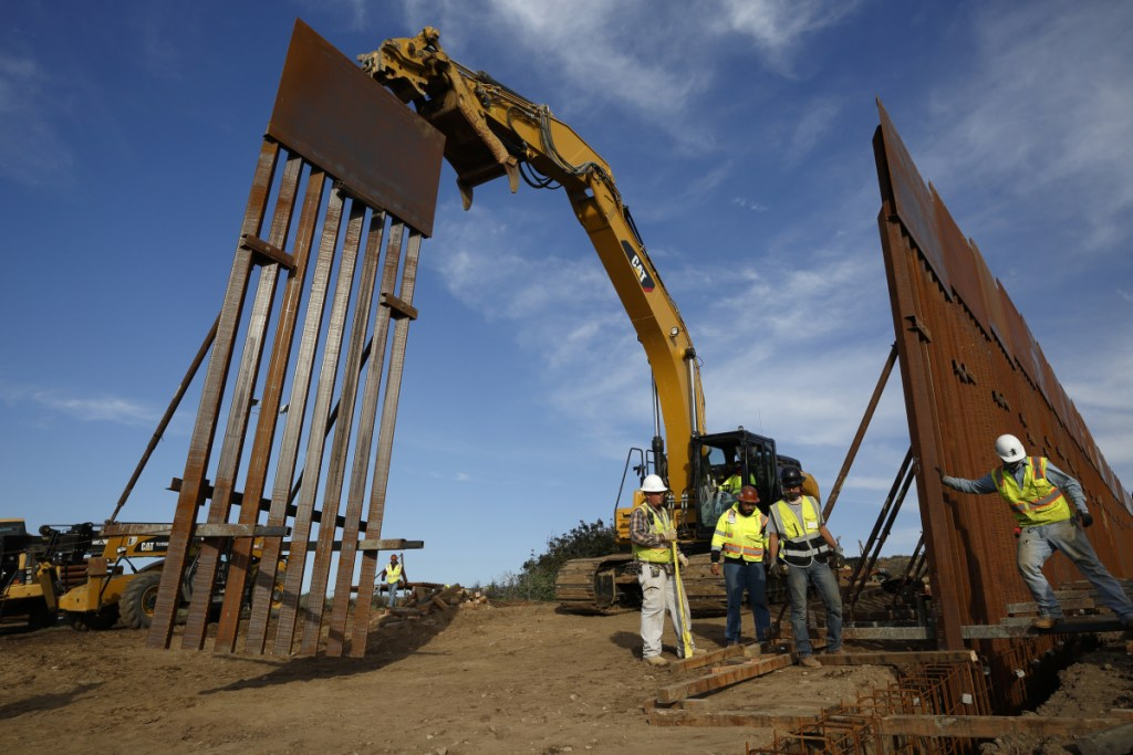 Construction crews install new border wall sections, seen from Tijuana, Mexico. Officials say President Trump is asking Congress for $8.1 billion for his dream project in his budget proposal to be unveiled Monday.