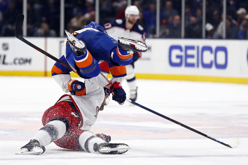 Islanders center Valtteri Filppula, top, trips over Blue Jackets left wing Nick Foligno during the first period Monday at Uniondale, N.Y. The Islanders won, 2-0.