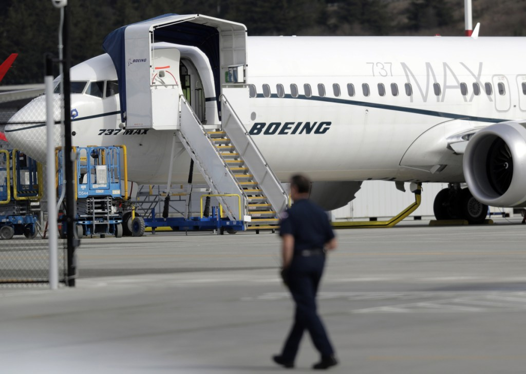 A worker walks next to a Boeing 737 MAX 8 airplane parked at Boeing Field in Seattle on Thursday.