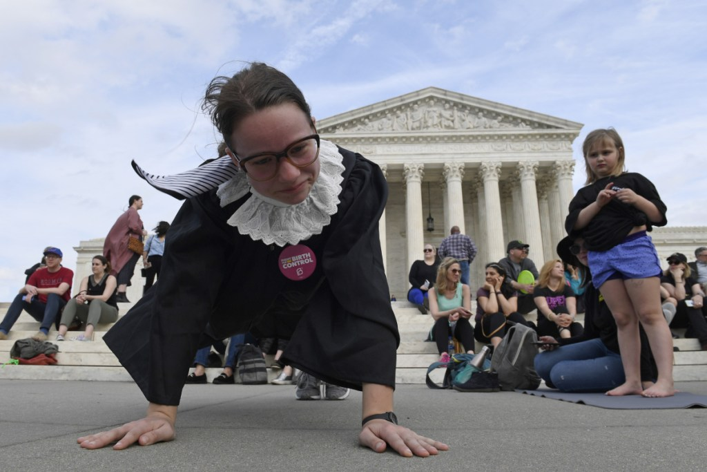 Alice Wisbiski, dressed as Supreme Court Associate Justice Ruth Bader Ginsburg, exercises on the steps of the Supreme Court in Washington on Friday, to celebrate Ginsburg's 86th birthday.