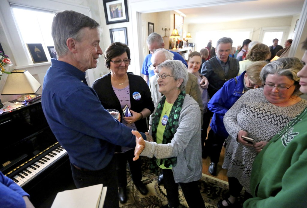 Former Colorado Gov. John Hickenlooper greets attendees during a visit to a Dubuque, Iowa, home earlier this month. As a teenager, Hickenlooper volunteered to work in Maine.
