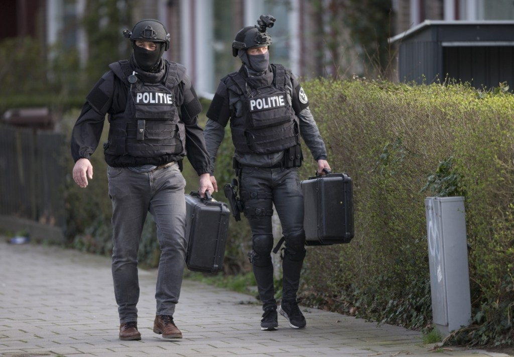 Dutch counterterrorism police leave after searching a house following the shooting incident Monday on a tram in Utrecht, Netherlands.