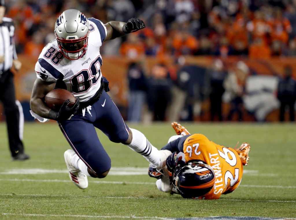 Tight end Martellus Bennett is tripped up by Broncos free safety Darian Stewart during a 2017 game in Denver. Bennett says he won't be coming out of retirement to rejoin the New England Patriots. (AP Photo/Jack Dempsey, File)