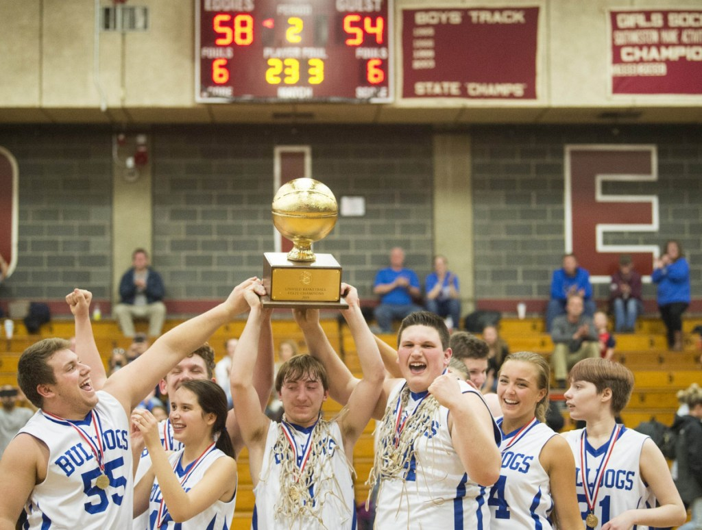 Madison's Scott Sawtelle hoists the Gold Ball with his teammates after they dethroned Westbrook 58-54 for the Unified title Tuesday. Unified basketball pairs students with and without disabilities, building ties that last off the court.