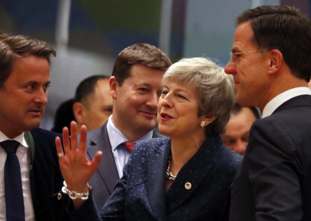 British Prime Minister Theresa May, center, speaks with Dutch Prime Minister Mark Rutte, right, and Luxembourg's Prime Minister Xavier Bettel on Thursday at an EU summit in Brussels. May persuaded European Union leaders to delay Brexit until May, just eight days before Britain was scheduled to leave the bloc.