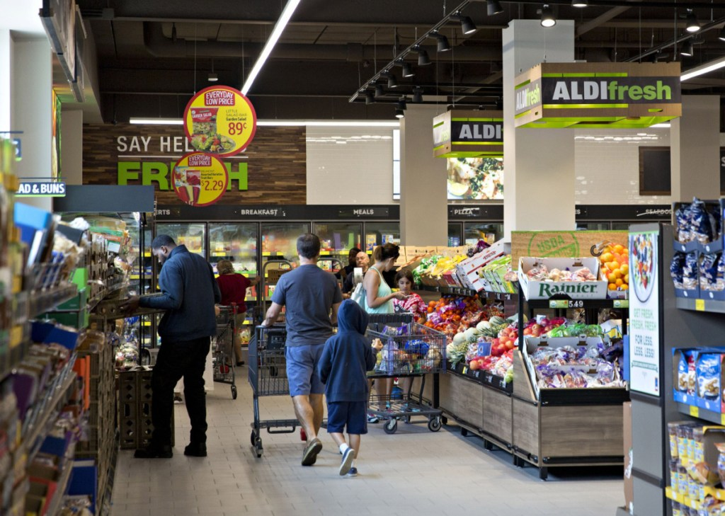 Shoppers walk through the fresh produce department at an Aldi food market in Chicago.