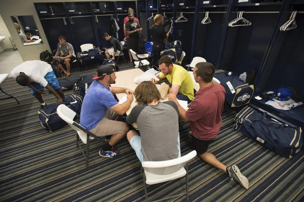 Members of the Biloxi Shuckers minor league baseball team eat lunch before practice at the Pensacola Blue Wahoos' stadium in Pensacola, Fla. Minor leaguers at the lowest levels can make as little as $1,100 per month despite spending 50-to-70 hours per week at the ballpark.