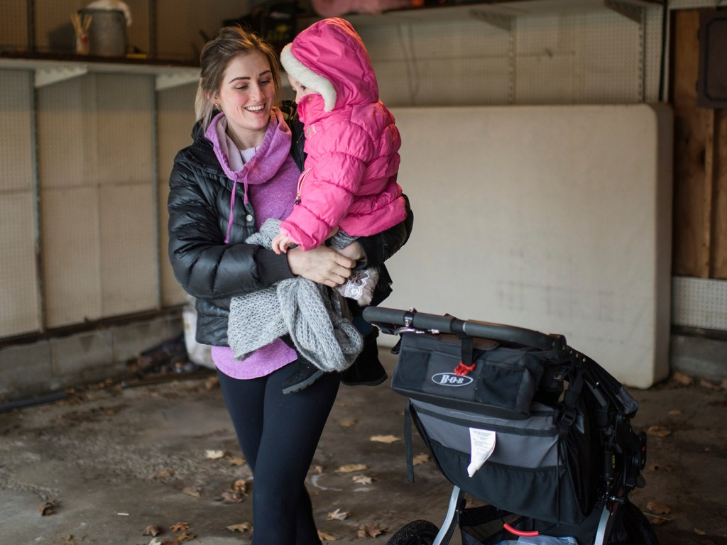 Tess Sawyer takes her 3-year-old daughter inside their house near Cleveland. Sawyer says she stopped using her BOB jogging stroller in February after learning about a lawsuit settlement.