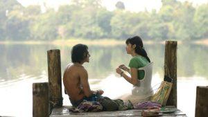 Kadr z filmu Mika przedstawiający głównych bohaterów - Mikę i Indi siedzących nad jeziorem, Mika siedzi w gorsecie na skoliozę.