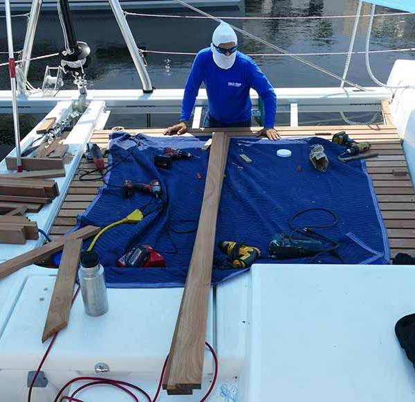 Multitech Technician Working on New Teak Deck for Catamaran