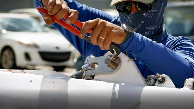 multitech mechanic repairing a catamaran