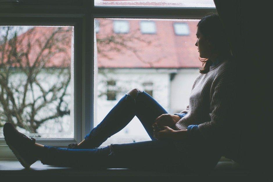 Frau sitzt am Fenster, Digitale Depression