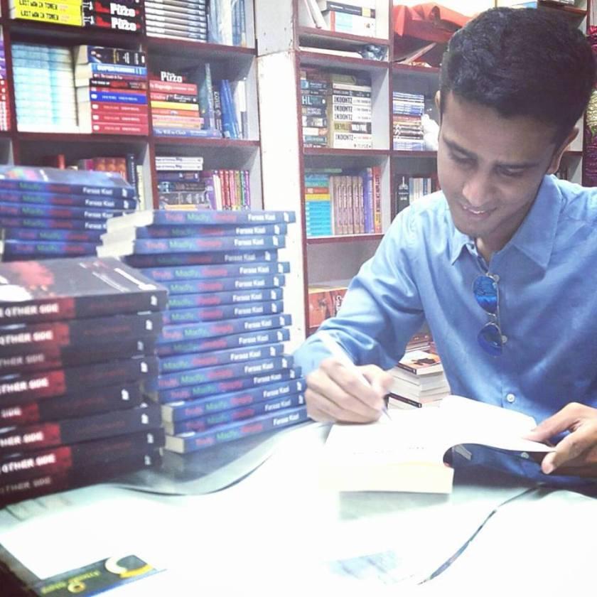 Photo showing Faraaz Kazi signing his books