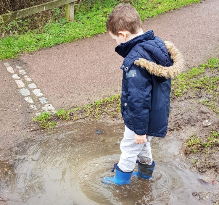 boy-in-blue-wellies-wading-in-muddy-puddle
