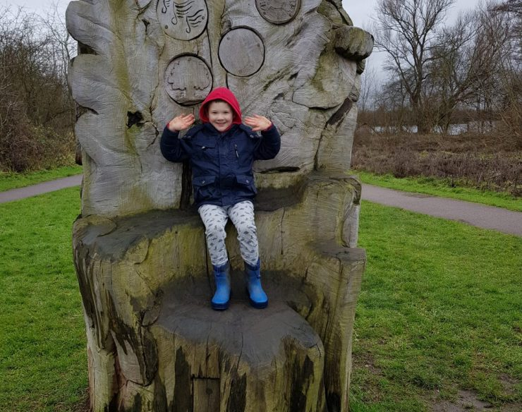 boy-sitting-on-carved-wooden-chair-in-country-park