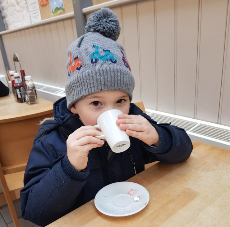boy-drinking-babyccino wearing-coat-and-hat