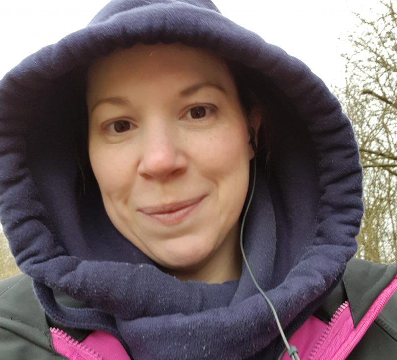 woman-with-hood-up-out-walking-with-headphones-in-ear