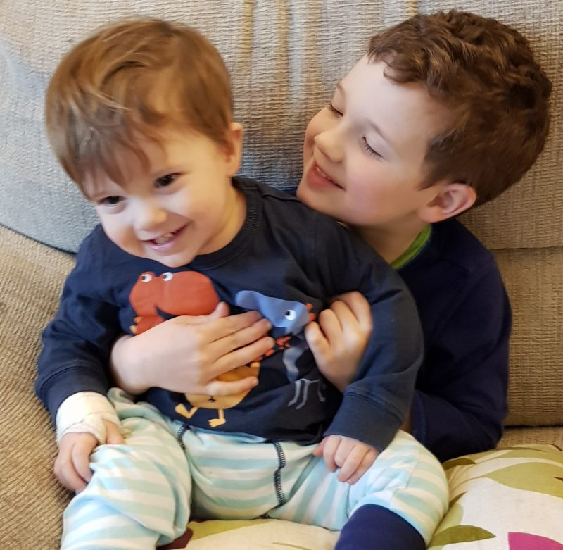 brothers-sitting-together-on-sofa-smiling-and-cuddling