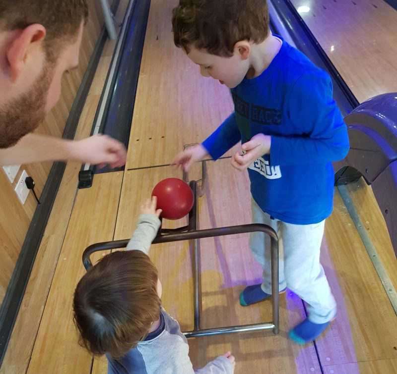 dad-and-older-son-helping-toddler-play-bowling