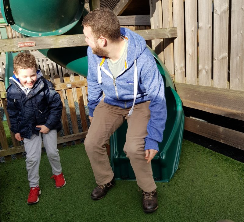 dad-and-son-laughing-at-bottom-of-tunnel-slide