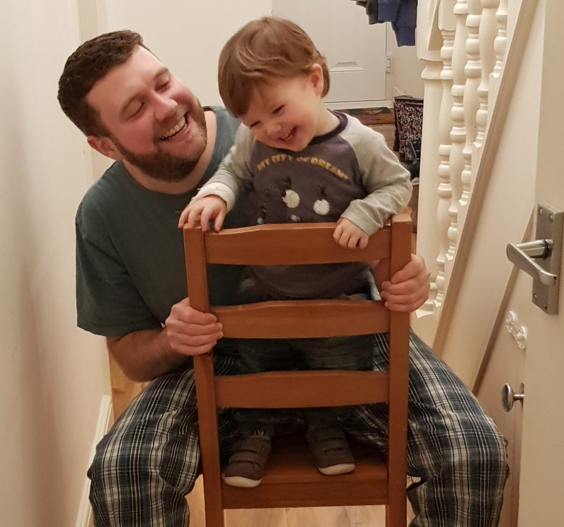 dad-and-toddler-son-sitting-on-chair-laughing