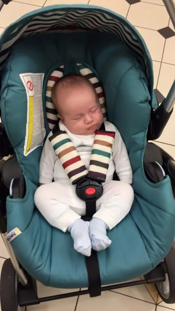 dexter as a newborn baby in his infant car seat wearing a white jumper and white pants and fast asleep. why we use a forward facing car seat.