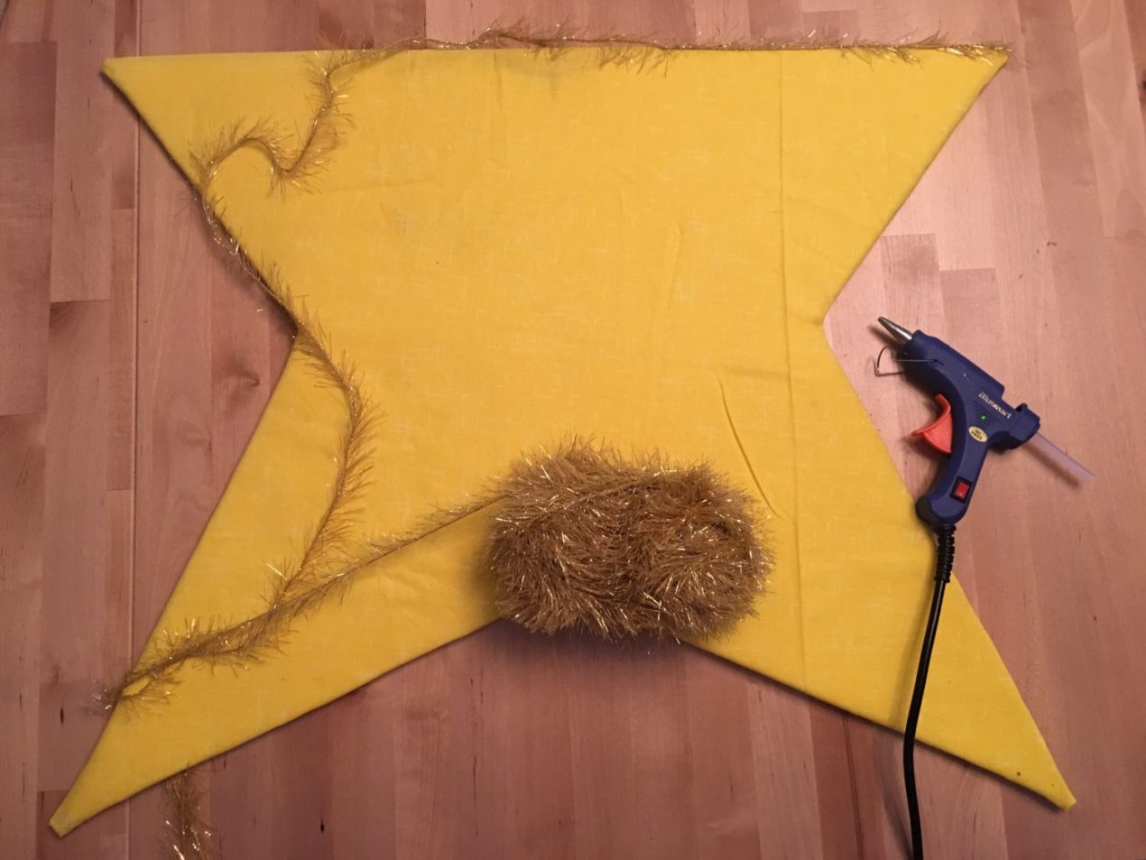 Decorating the DIY star with gold yarn