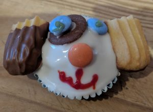 A cupcake decorated to look like the face of a dog. White icing, large chocolate button for a patch with two blue smarties for eyes, a orange smartie for the nose, red writing icing for a mouth and biscuits for ears