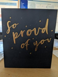 Black card with the words 'so proud of you' in gold