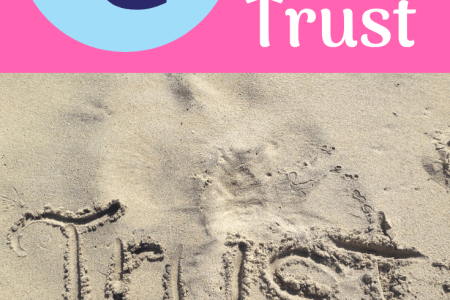 The word trust written in the sand.