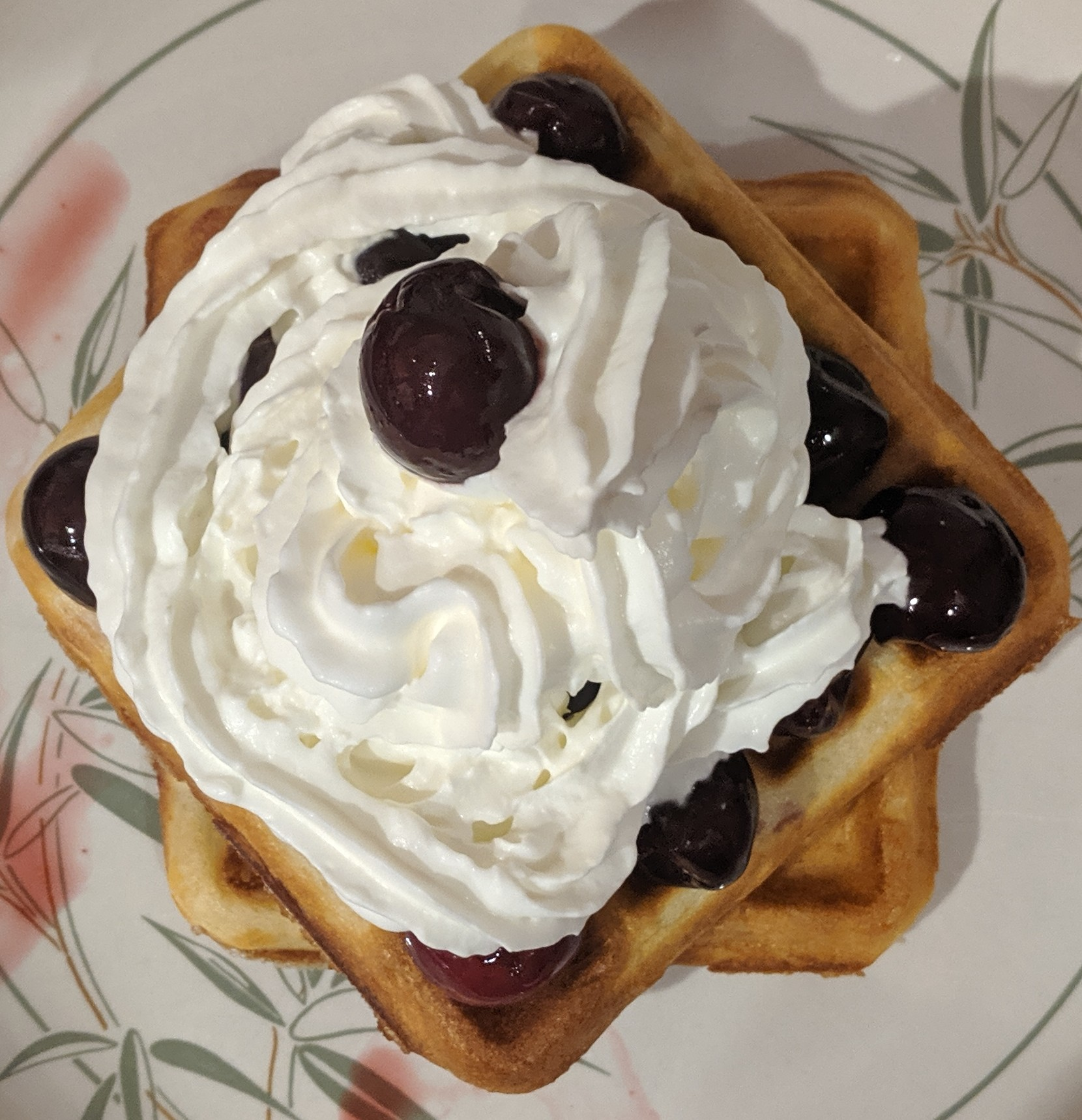 two waffles covered in cherries and cream