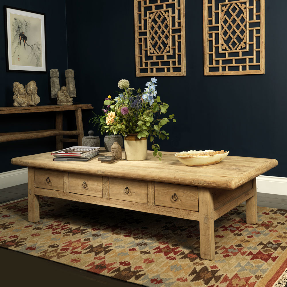 Coffee table with draws in the center of a room on a rug