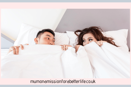 Man and woman peeping out the top of a duvet cover