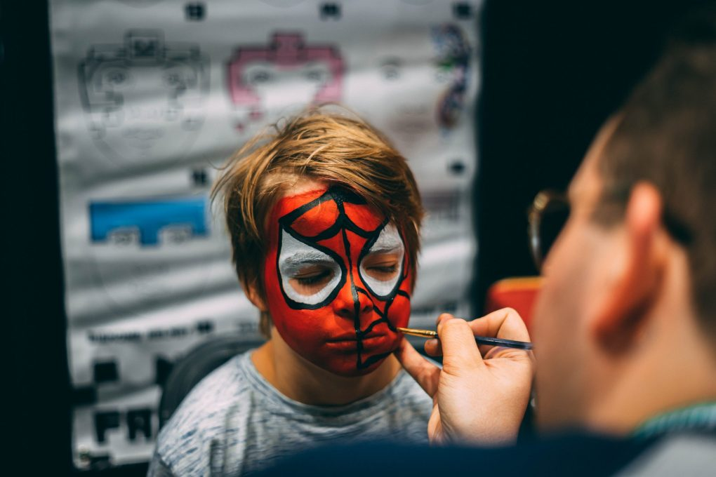 Boy having face painted to look like spider man