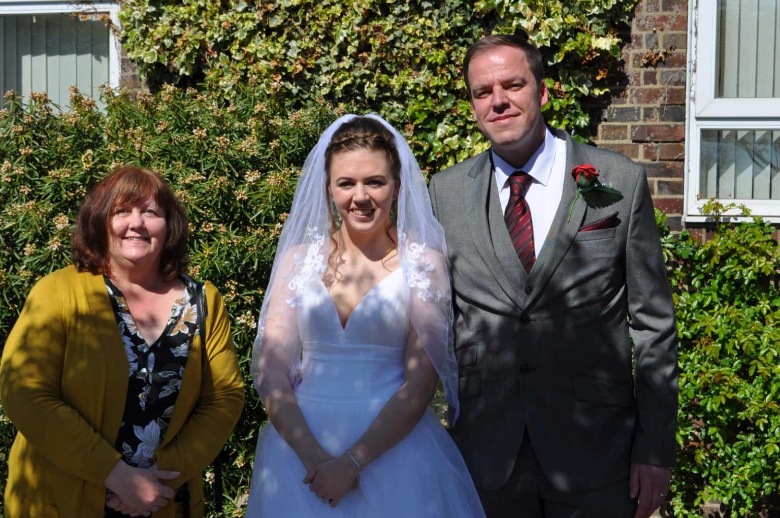 Bride and groom with a guest at a COVID wedding