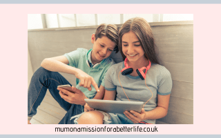 two teens sitting looking at a tablet screen.
