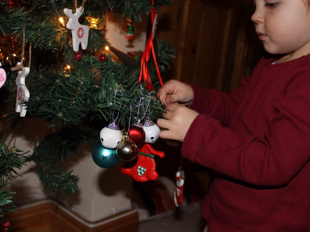 Toddler decorating Christmas tree