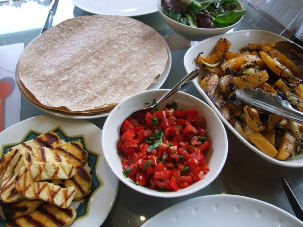 Table of food with Halloumi, tomatoe salad and sweet potatoe fries in bowls