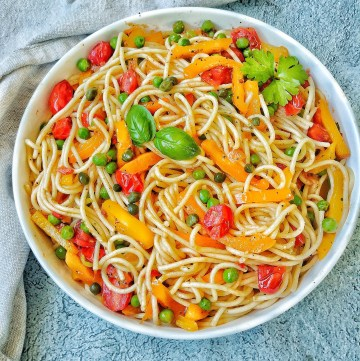 Bowl of Spaghetti with tomatoes, basil, bell peppers and peas.