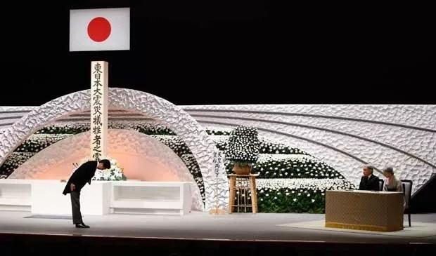 O premiê japonês, Shinzo Abe, se curva diante do casal de imperadores durante cerimônia em Tóquio (Foto: Kyodo)